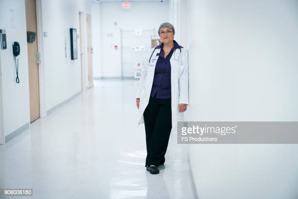 mixed race doctor leaning on hospital wall - leaning stock pictures, royalty-free photos & images