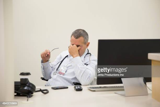 Mixed race doctor rubbing his eyes in office