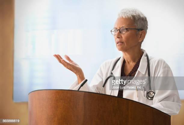 Mixed race doctor speaking at podium