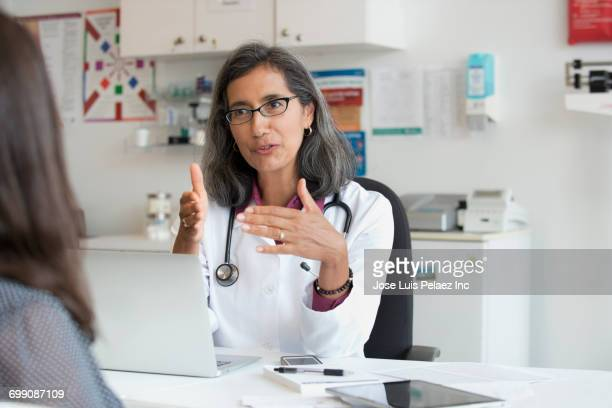 mixed race doctor talking to patient - female doctor stock photos and pictures
