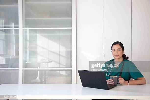 Mixed race doctor using laptop