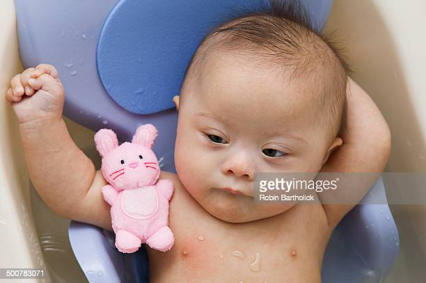 Mixed race Down Syndrome baby laying in plastic bathtub