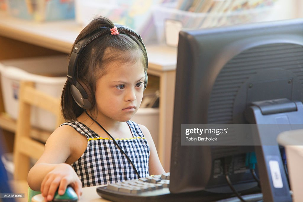 Mixed race Down syndrome student using computer : Stock Photo