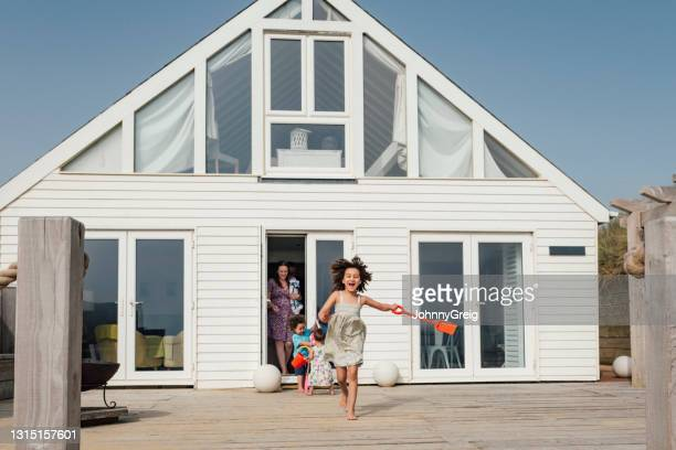 mixed race elementary age girl leading family to the beach - childhood stock pictures, royalty-free photos & images