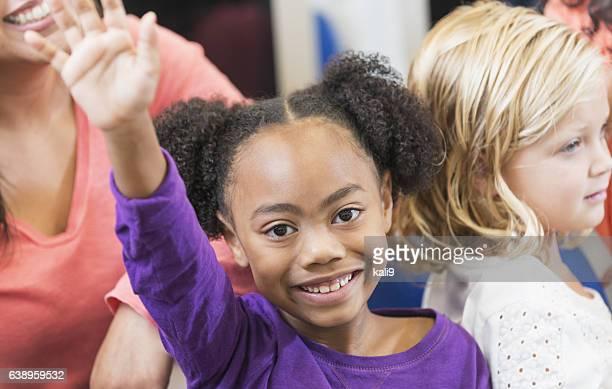 Mixed race elementary school girl raising hand in class