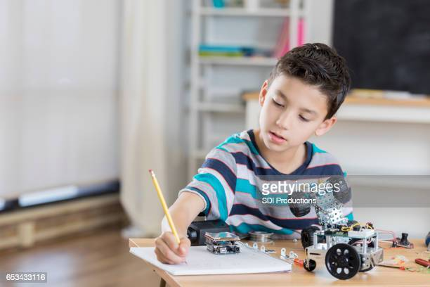 Mixed race elementary student works on robotics project