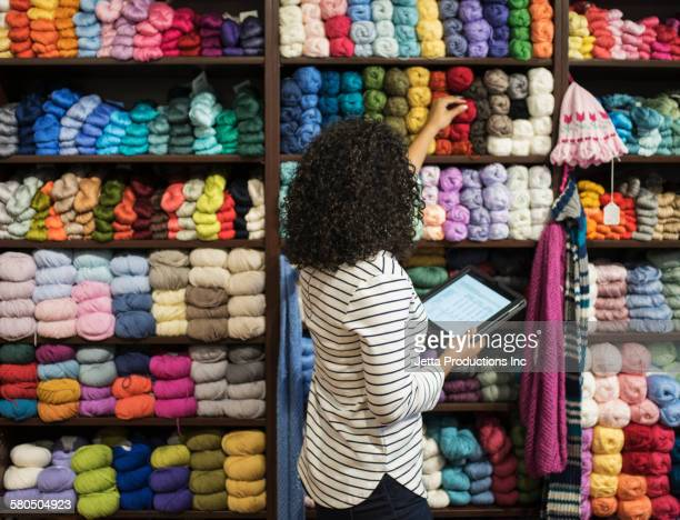 Mixed race entrepreneur taking inventory in yarn store