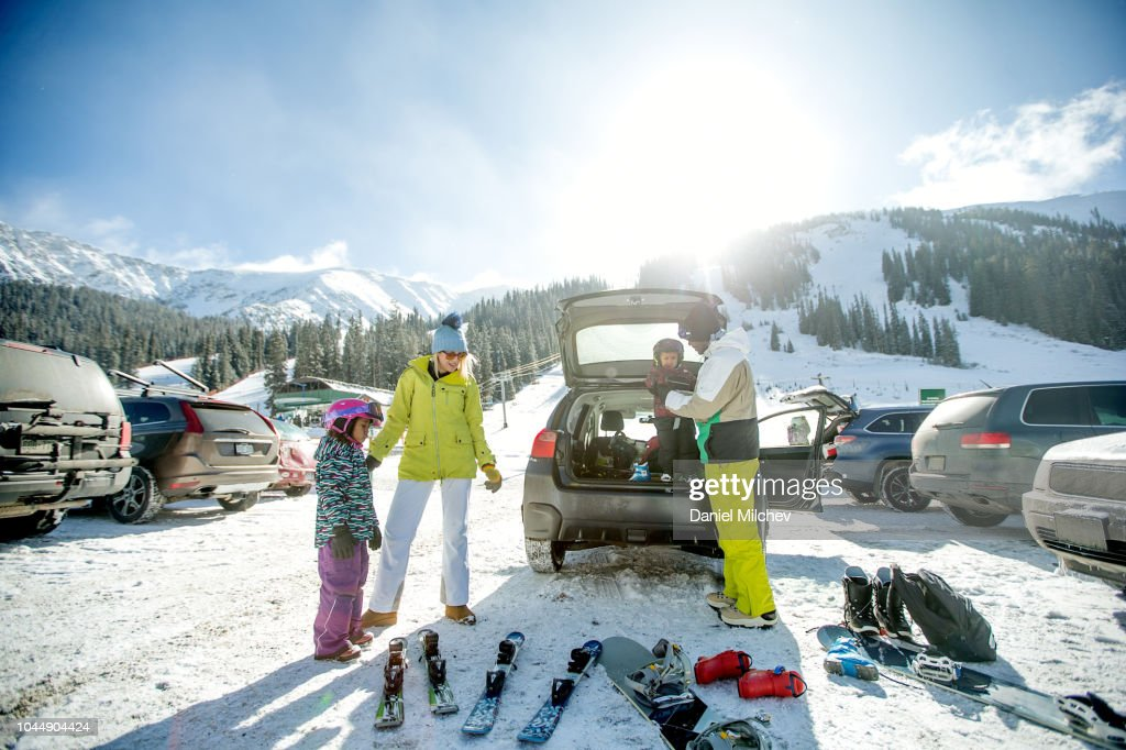 Mixed race family at a parking lot unloading ski and snowboard equipment out of their car and getting the kids ready for a day on the mountain. : Foto de stock