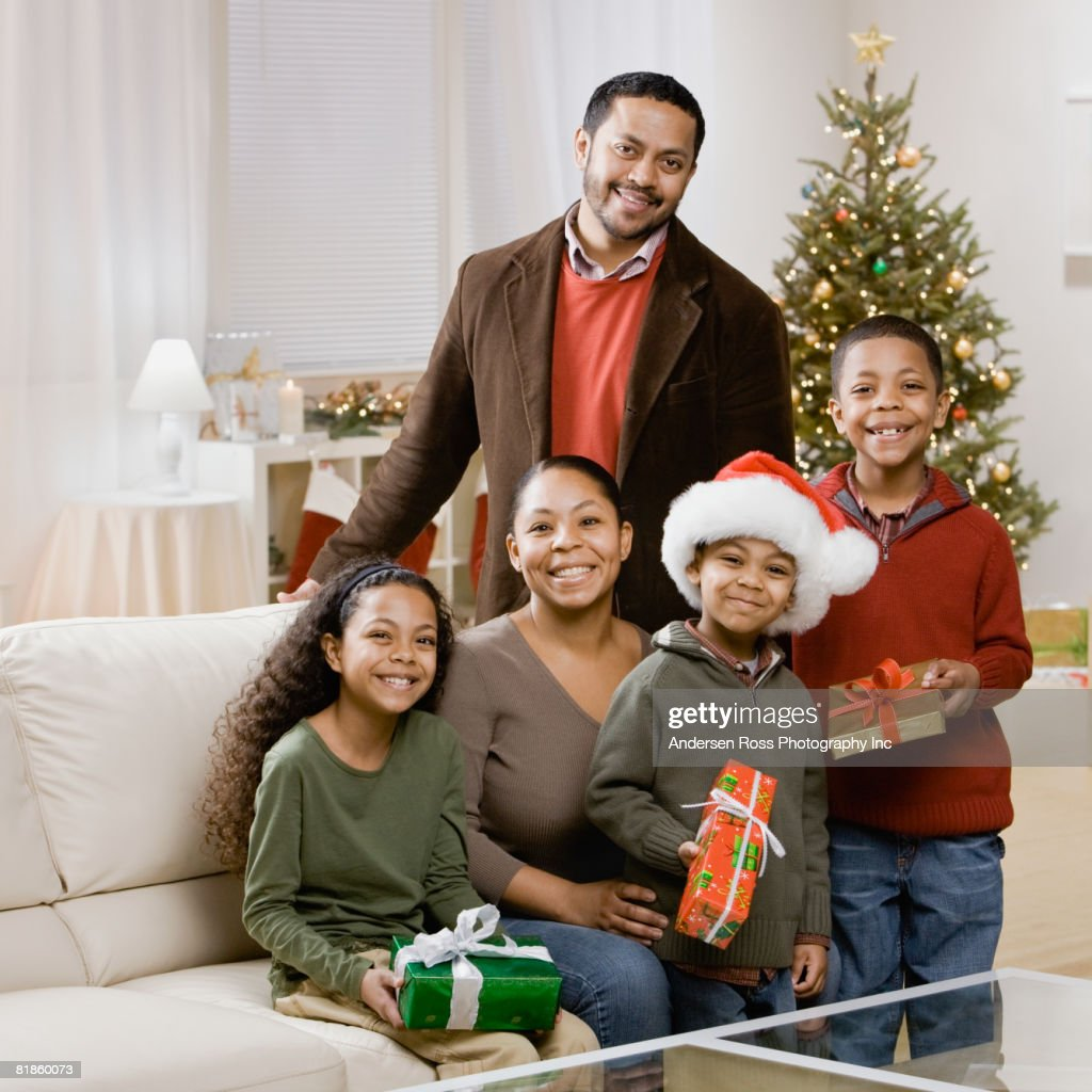 Mixed Race Family Holding Christmas Gifts Stock Photo | Getty Images