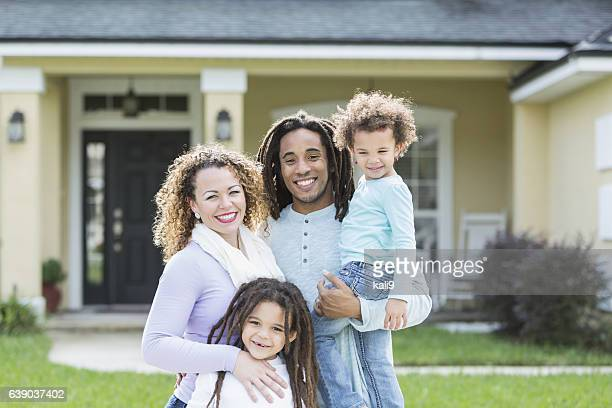 Mixed race family of four in front of home