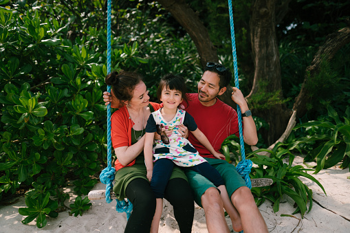 Mixed race family on swing on beach, Japan - gettyimageskorea