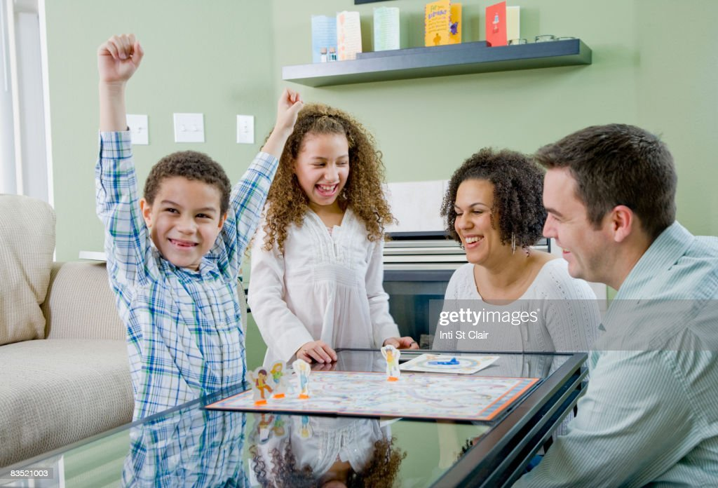 Mixed race family playing board game : Foto de stock