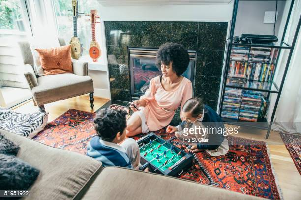 Mixed race family playing foosball on living room floor