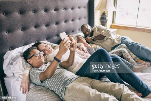 Mixed race family relaxing on bed together during the day