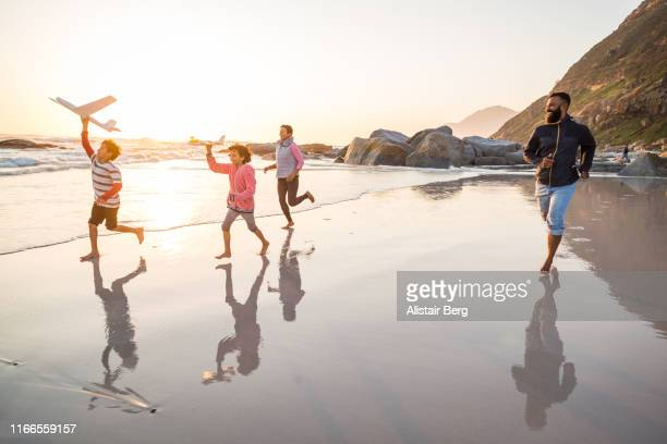 mixed race family running along beach with toy planes - reportaje imágenes stock pictures, royalty-free photos & images