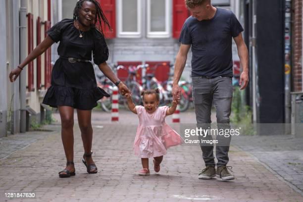 a mixed race family walking through the city with their young daughter - color blindness - fotografias e filmes do acervo