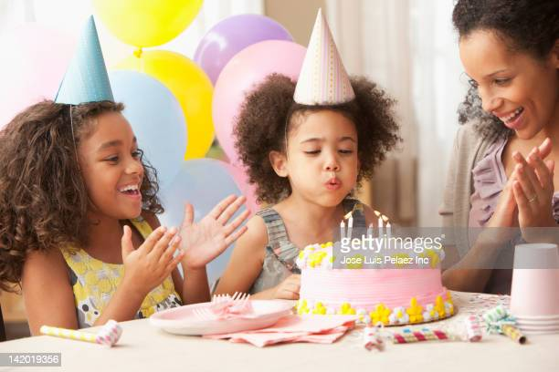 mixed race family watching girl blow out birthday candles - birthday candle stock pictures, royalty-free photos & images