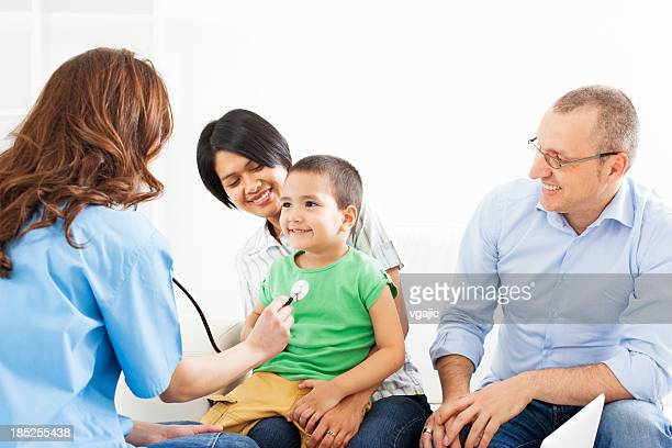 Mixed race family with child visit doctor.