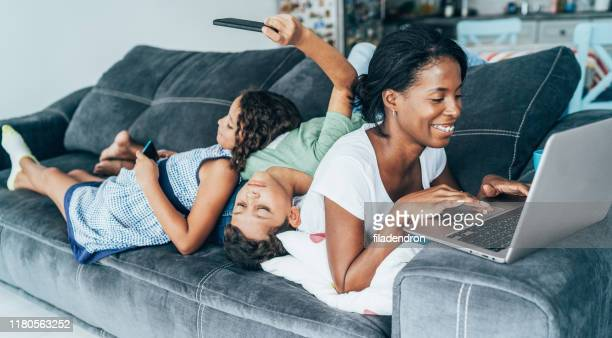 mixed race family with digital devices - family at home stock pictures, royalty-free photos & images