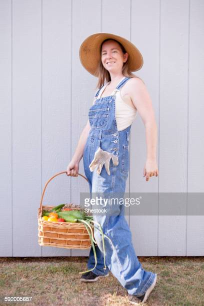Mixed race farmer holding basket of vegetables