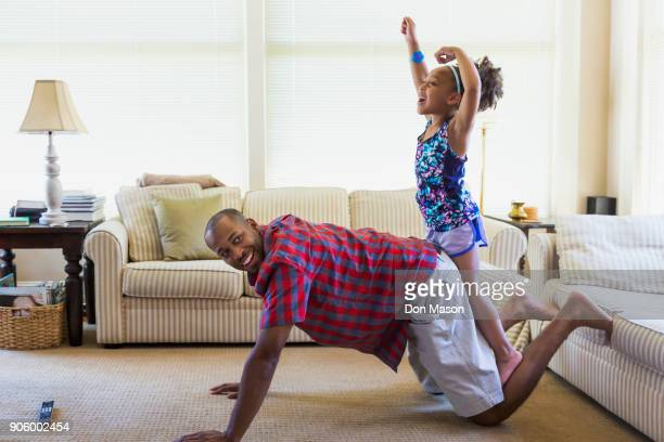 mixed race father and daughter playing on floor in livingroom - barefoot black men stock pictures, royalty-free photos & images