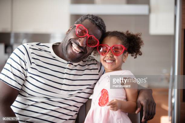 mixed race father and daughter taste lollipop during valentine's day - valentine's day stock pictures, royalty-free photos & images