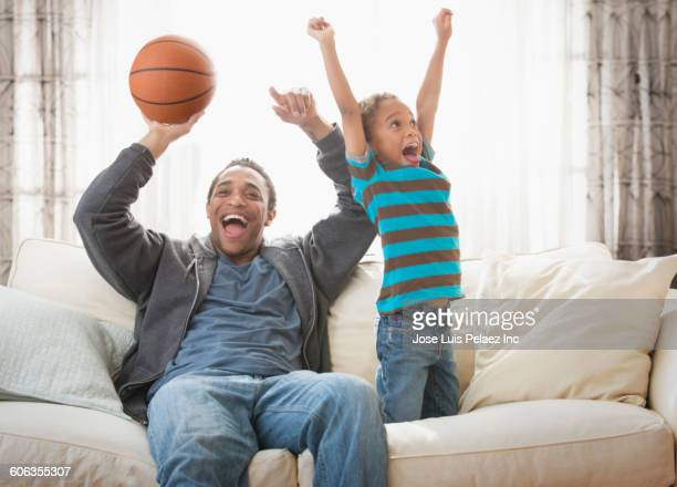 mixed race father and son cheering with basketball on sofa - family watching tv stock pictures, royalty-free photos & images