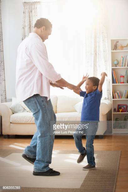 Mixed race father and son dancing in living room