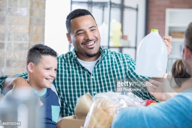 混血の父と息子は、フード ドライブ中にアイテムを寄付します。 - ヤードポンド法 ストックフォトと画像