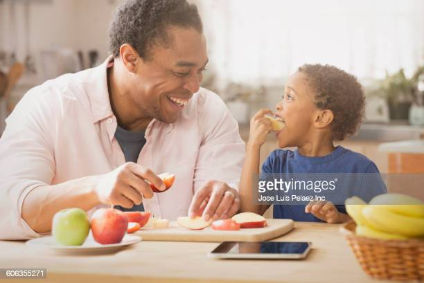 Mixed race father and son eating apples in kitchen