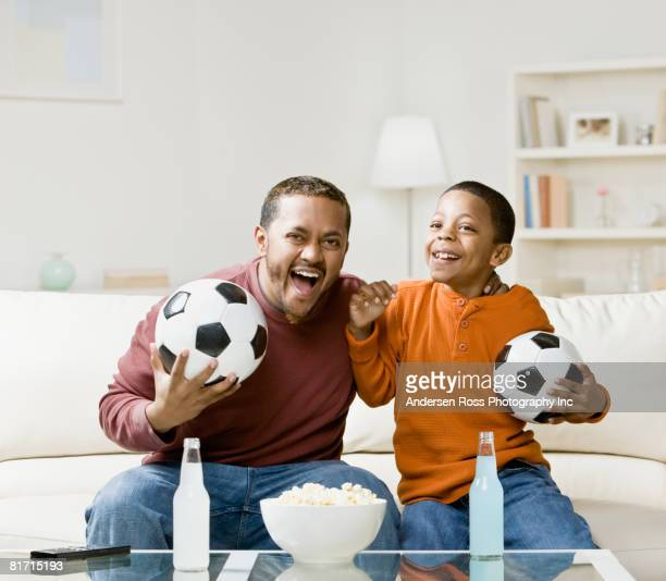 Mixed Race father and son holding soccer balls