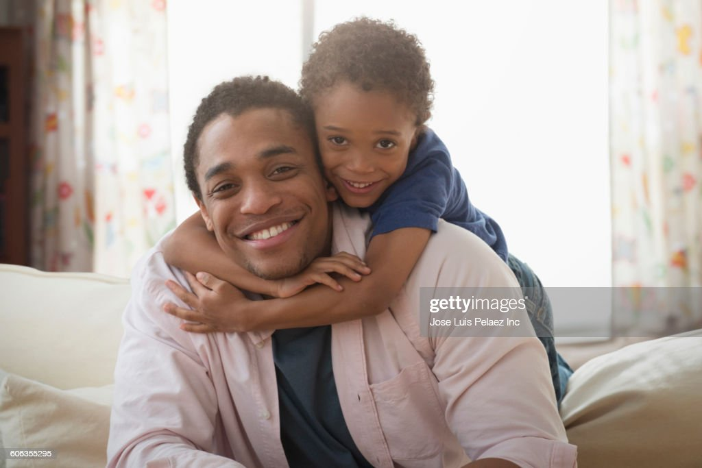 Mixed race father and son hugging on sofa : Stock Photo