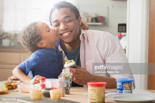 Mixed race father and son icing cupcakes in kitchen