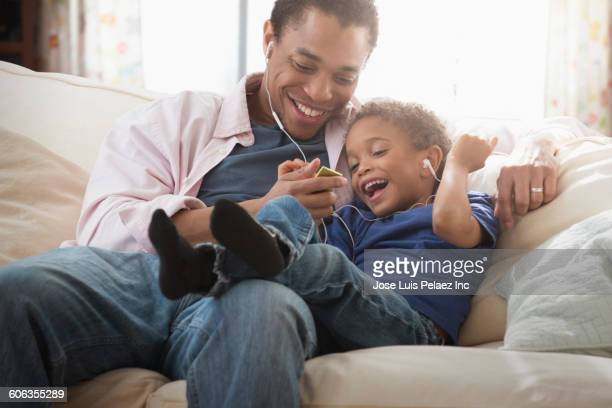 Mixed race father and son listening to earbuds on sofa