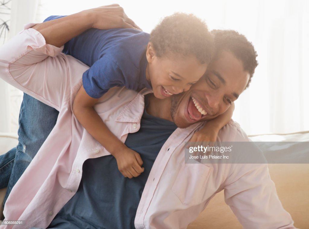 Mixed race father and son playing on sofa : Stock Photo