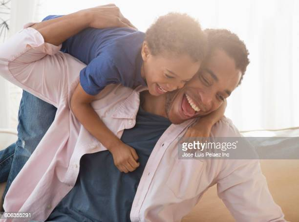 mixed race father and son playing on sofa - naughty america - fotografias e filmes do acervo
