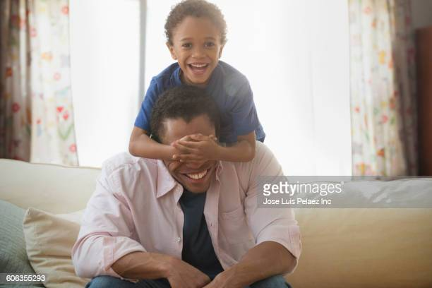 Mixed race father and son playing on sofa