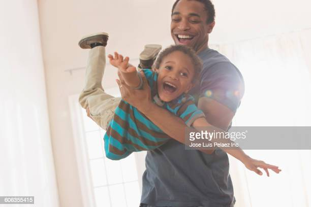 Mixed race father and son playing