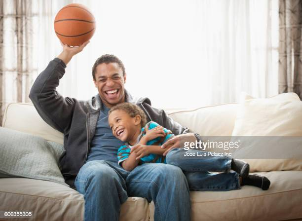 Mixed race father and son playing with basketball on sofa