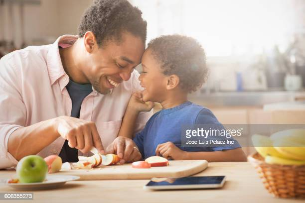 Mixed race father and son slicing apple in kitchen