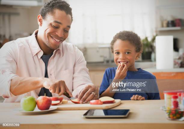 Mixed race father and son slicing apples in kitchen