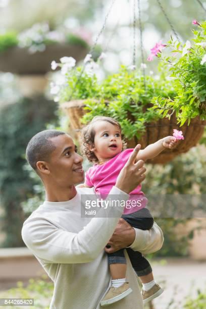 Padre de raza mixta con niña para flores