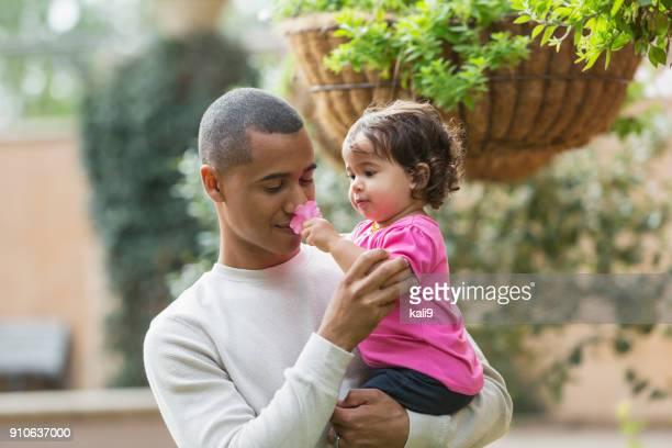 Padre de raza mixta con niña que huele una flor