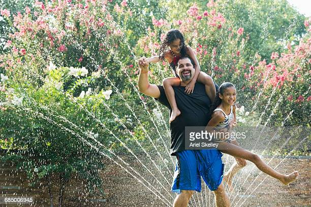 Mixed Race father holding daughters in backyard sprinkler