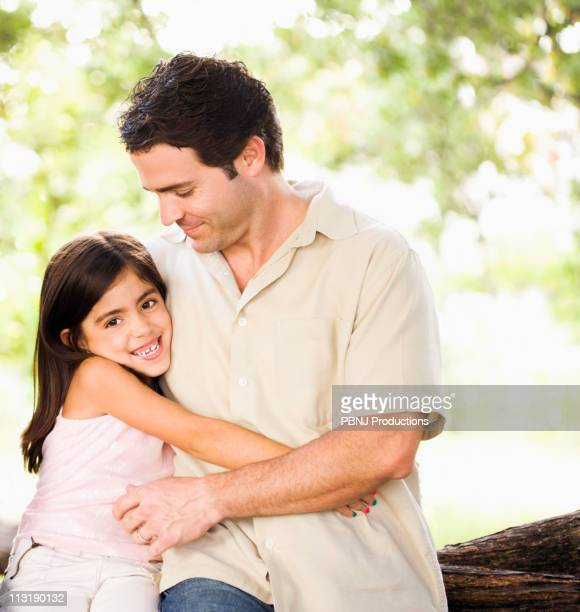 Mixed race father hugging daughter