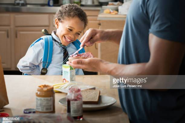 Mixed race father making lunch for son in kitchen