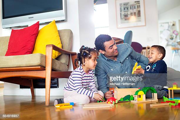 mixed race father, son,daughter playing at home