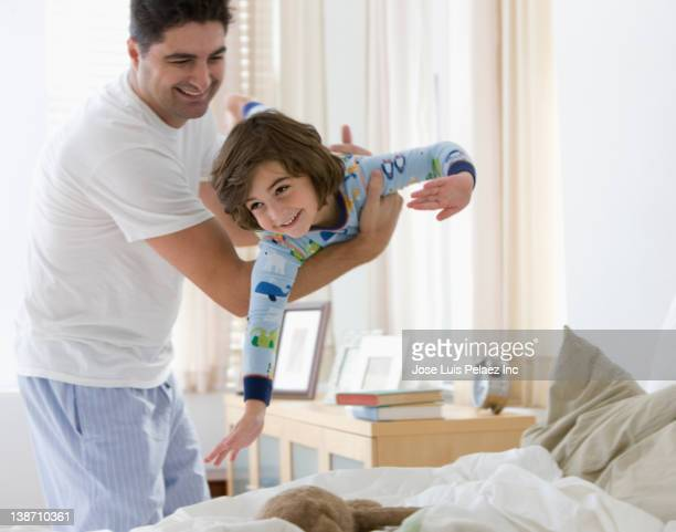 Mixed race father swinging son in bedroom