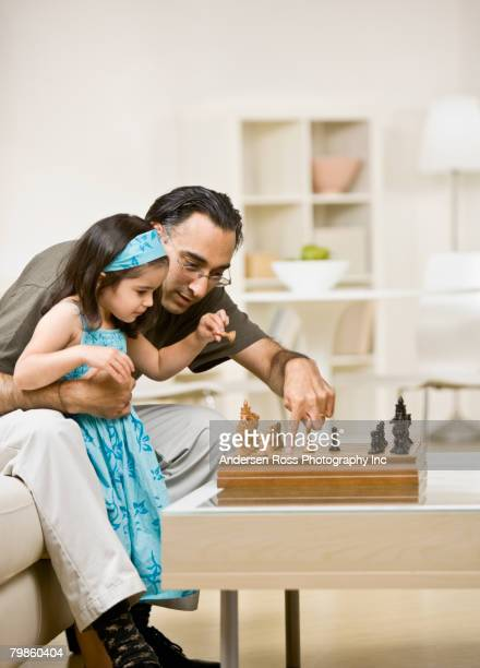 Mixed Race father teaching daughter to play chess