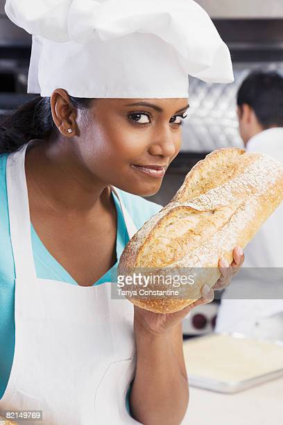 Mixed Race female baker smelling fresh bread